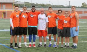 group of athletes and their coach smiling
